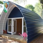 arched cabins quonset hut homes in blue and painted scheme featuring glass door and windows
