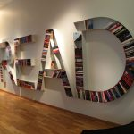 artistic cool bookshelves idea in letter shape with colorful tone mounted on white wall