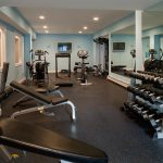 awesome looking home gym essentials with blue painted wall and mirrors on wall