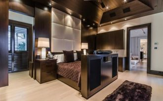 best and luxurious mansion design bedroom with balck glossy frame and brown sheet and wooden ceiling with padded headboard and wooden floor