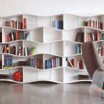 best cool bookshelves deisgn in wavery shape in white color on the wall with reclining chair