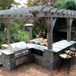 best gray outdoor kitchen layout idea iwth stone kitchenette and black iron vintage stools beneath the wooden pergola with green surrounding