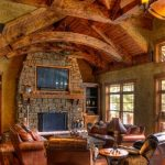 best interior design of country house idea with glass window and crafted wooden ceiling with stone fireplace mantel and red leather sofa