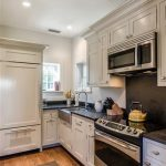 best white stone house kitchen design with wooden cabinetry and black backsplash and wooden floor and gray runner rug