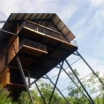 best wooden house design with black iron pole and wooden flooring hovering on the air above the forest