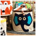 blue-elephant-and-orange-fox-storage-bins-by-3-sprouts-near-wooden-crib-and-on-grey-rug-and-full-toys-and-bag-in-the-bin