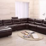 brown leather long sectional sofa with chaise in one side plus small round rug plus stunning wooden laminate floor