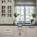 classic kitchen design with white carved wooden cabinet and patterned black and white blind on the glass window
