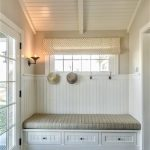 comfortable banquette idea in a stone house design with hat hooks and tile flooring and storage and glass door