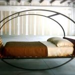 comfortable bedding design in round shape with rolled model and brown white sheet in spacious room with open plan