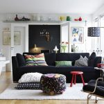 comfortable scandinavian decor design in living room with black sofa with floral pouff and glass window and curved floor lamp