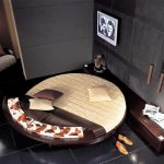 comfortable yellow and brown round bed design with tv screen and long wooden console table and gray tile flooring