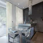 contemporary-kitchen-island-with-stainless-steel-countertops-and-stainless-steel-appliances-and-flat-panel-cabinets-with-a-table-slide-inside-the-island