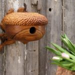 creative-and-decorative-Bird-House-Handmade-From-Wood-with-Acorn-design-for-outdoor-decor-mounted-on-the-wooden-fence