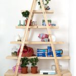 diy ladder shelving unit in natural finish adorned with fresh potted plant and books plus piggy bank decorated in the corner of the room with wood floor
