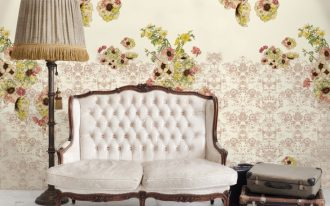 elegant and classy white sofa with tufted backrest and floor lamp and suitcase end table and floral wall decor