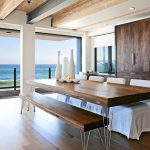 elegant and spacious beach dining room design with wooden table and wooden bench and slipcovered chairs on wooden floor