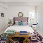 elegant bedroom idea with white bedd8ing and wooden bench and patterned purple area rug and glass window and wall mirror