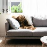 elegant gray apartment sectional sofa idea design with faux furry throw and cushion and round white coffee table and wooden floor
