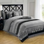elegant gray bedroom design with large glass window and wooden floor and white table lamp and tall headboard and gray california king bed comforter set