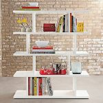 elegant white freestanding bookshelves design with assymetrical slot before brick wall