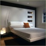 elegant white worth platform bed with orange pillow and white headboard and table lamps