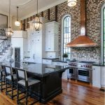 european kitchen loft design idea with brick wall accent and wooden floor and black island and gray chairs and pendants and arched glass window