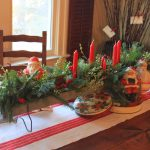 exotic and beautiful christmas centerpiece design with candelabrum and clematis plant and white red table cloth on wooden dining table