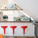 flashing bright red scandinavian bar stools with white island beneath sloping ceiling in the loft with white cbainet and wooden floor