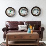 golden and black small convex mirror on white brick wall together with brown leather love seat sofa and wooden coffee table with two drawers and one shelf underneath