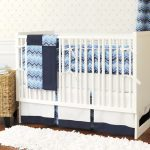 gorgeous baby nursery design with white crib and blue chevron quilt and rattan storage and faux white fluffy rug