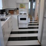 gorgeous black and white stripe patterned tile flooring in the kitchen with white cabinet and glass window