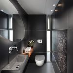 gorgeous black bathroom design with oval shaped wall mirror and wall painting and floating minimalist vanity and unique lighting