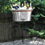 gorgeous bronze baverage tub with stand design and black iron scrolled on rustic wooden deck aside fence with greenery