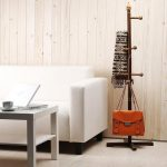 gorgeous classic wooden standing coat rack on wooden floor with white couch and white coffee table and wooden siding