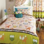 gorgeous creamy and green owl bedding sheet in bedroom with wooden floor and glass window and owl printed curtain