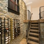 gorgeous hallway decoration idea with stone siding and glass ventilation and woodne staircase and wine racks