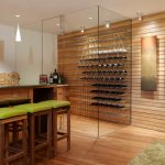 gorgeous kitchen bar design with wooden table and green stools and wooden siding and walk in wine rack idea