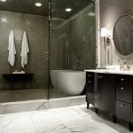 gorgeous rustic and luxurious modern bathroom with round wall mirror and walk in shower and shaded white wall lamps