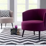 gorgeous soft pink accent chair with purple combination and chevron cushion and area rug and pile books coffee table