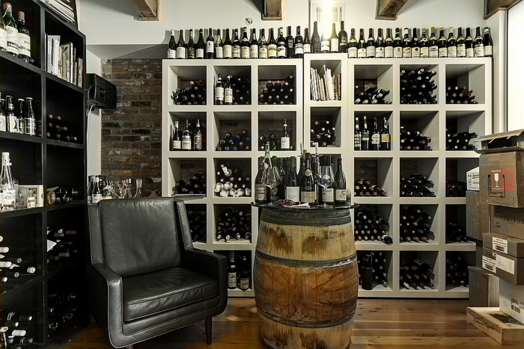 gorgeous vintage cellar design with barrel coffee table and black leather sofa and white wine rack