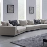 gorgeous white interior design with long white sectional sofa design and black patterned cushion and glass window and wall picture