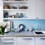 gorgeous white kitchen design with blue small tile mosaic backsplash and white upper cabinet and indoor plant