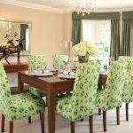gorgeous wooden dining table with green patterned  slip cover for dining room chairs design and luxurious chandelier