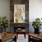 interior design with wooden coffee table and gray arm chairs and wooden floor and indoor potted plants and fireplace