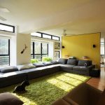 interior design with yellow painted room divider and green area rug and long gray sectional sofa design with wooden floor