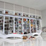 large built in bookshelves design in personal library idea with colorful decoration and white relaxing chairs and white floor