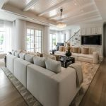 Lavish Mansion Design With Long Luxurious White Sectional Sofa Design With Creamy Patterned Area Rug And Black Coffee Table And Wooden Floor And Open Plan