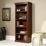 long shaped contemporary wooden free standing bookshelves with five level shelves with upholstered chair for relaxing plus black ceramic accessories