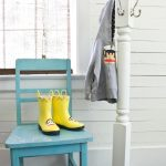 lovable blue chair with yellow boots and white standing coat rack beneath white siding